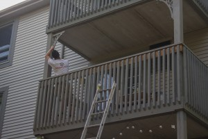 ArmourCo employee reaching up to paint a decorative support post on a second story balcony